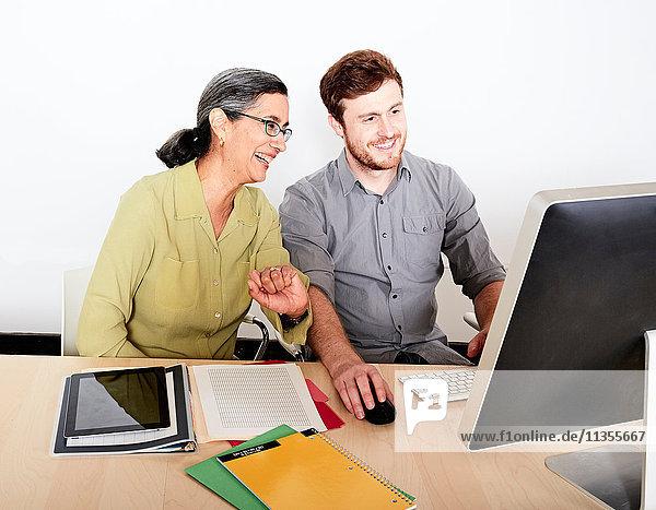 Kollegen schauen lächelnd auf den Computermonitor