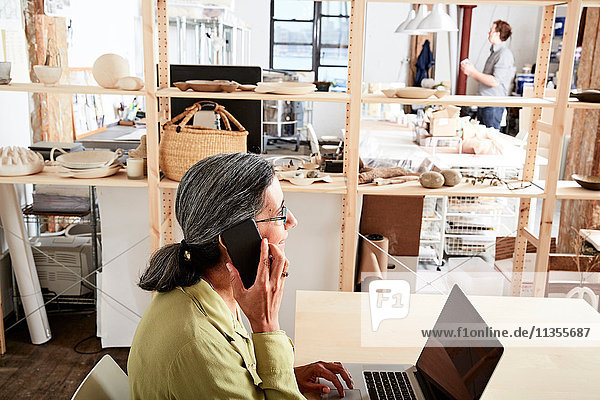 Woman in workshop using phone and laptop