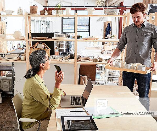 Mann zeigt Kollege Tablett aus Keramik