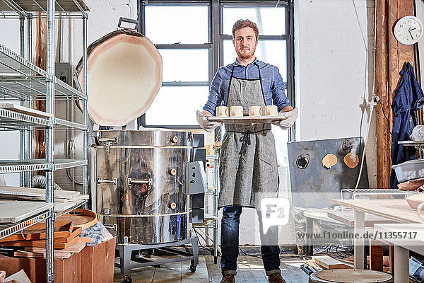 Töpfer in der Werkstatt mit einem Töpfertablett nach Brennofen