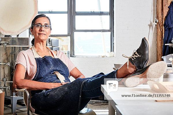 Frau sitzt mit erhobenen Füßen in Töpferwerkstatt