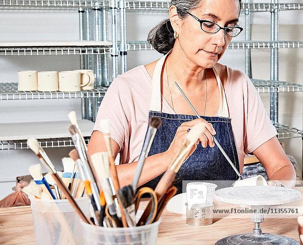 Frau in Werkstatt bemalt Töpferei
