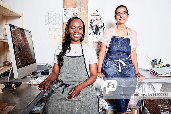 Woman at desk wearing aprons looking at camera smiling