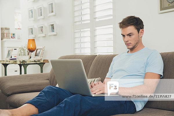 Mann auf Sofa mit Laptop