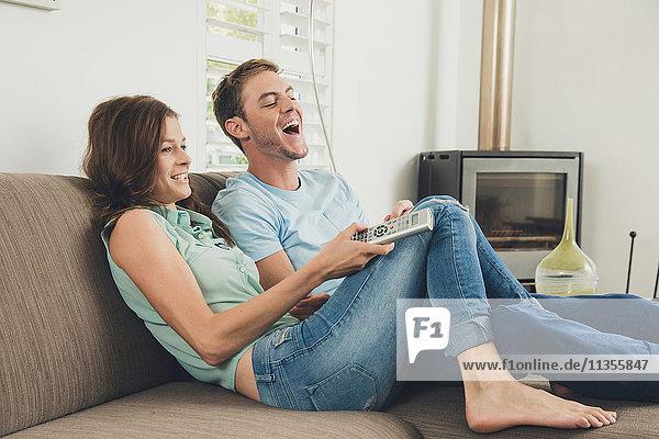 Paar auf dem Sofa mit Fernbedienung lacht