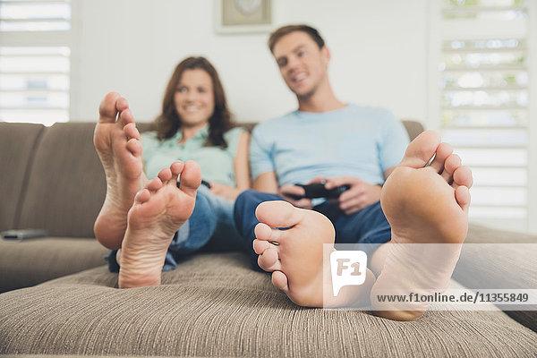 Paar barfuss auf dem Sofa mit Videospiel-Controller