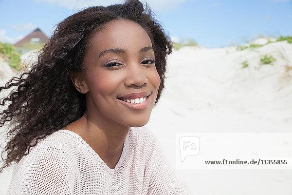 Junge Frau am Strand an einem windigen Tag