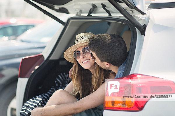 Paar im Kofferraum küsst sich