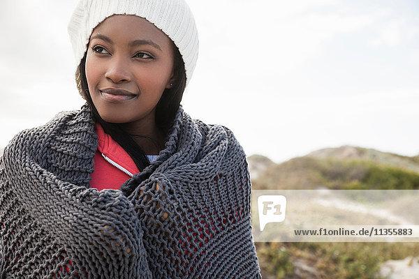 Junge Frau in ein Strickschal gehüllt an einem kalten Tag