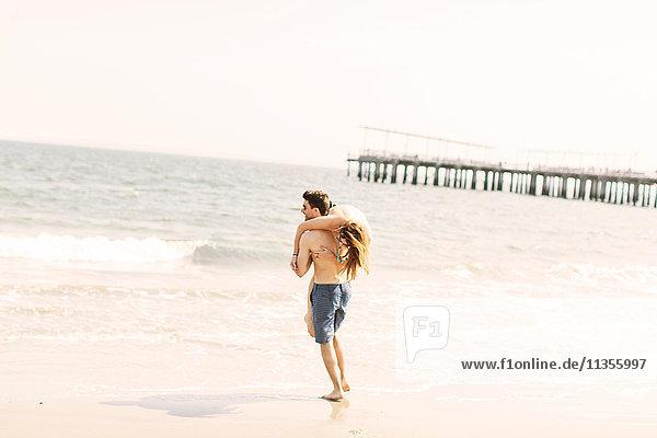 Man on beach carrying woman on shoulder to ocean  Coney island  Brooklyn  New York  USA