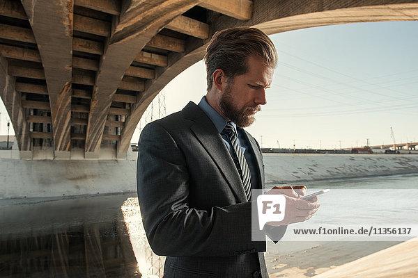 Geschäftsmann beim Schreiben von SMS  Los Angeles River  Kalifornien  USA