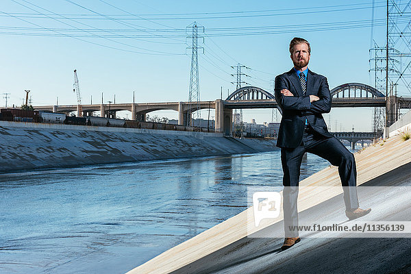 Businessman arms crossed  looking at camera  Los Angeles river  California  USA