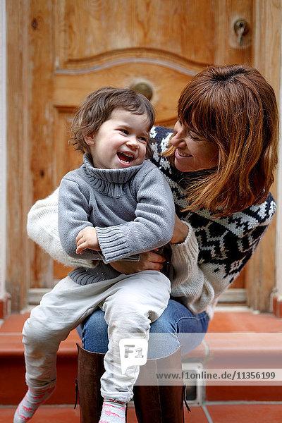 Mutter und Tochter vor der Tür lachend