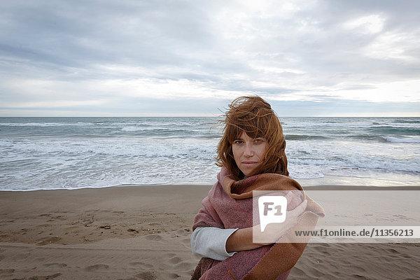 In eine Decke gewickelte Frau am Strand  die in die Kamera schaut