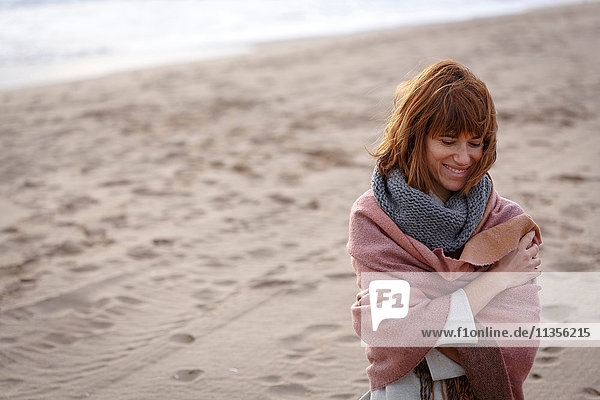 Woman on beach wrapped in blanket looking down smiling