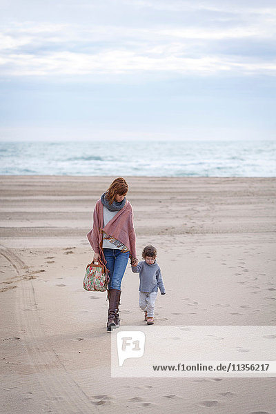 Mother and daughter walking on beach holding hands