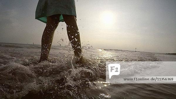 Beine einer Frau an der Küste beim Spaziergang im Meer