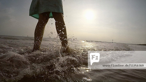 Legs of woman on coastline walking in ocean