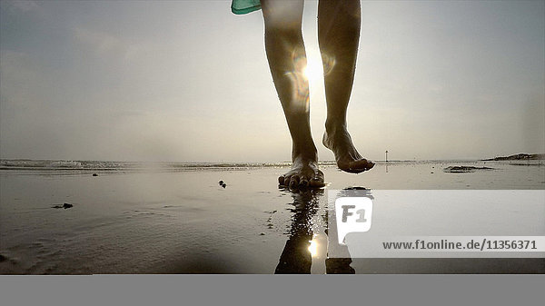 Beine einer Frau  die am nassen Strand spazieren geht