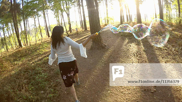 Rear view of woman in forest running with bubble wand