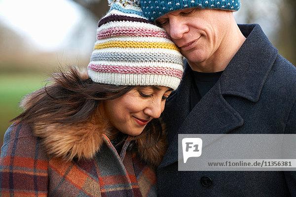 Mature couple wearing knit hats hugging