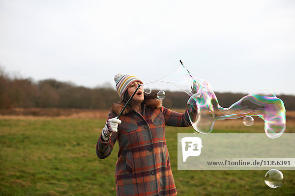 Woman in field using bubble wands to make bubbles