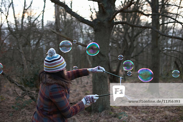 Woman in forest using bubble wands to make bubbles