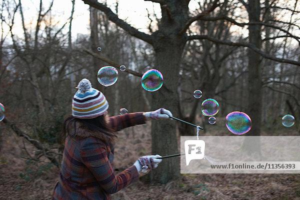Frau im Wald mit Blasenzauberstäben zum Blasenmachen