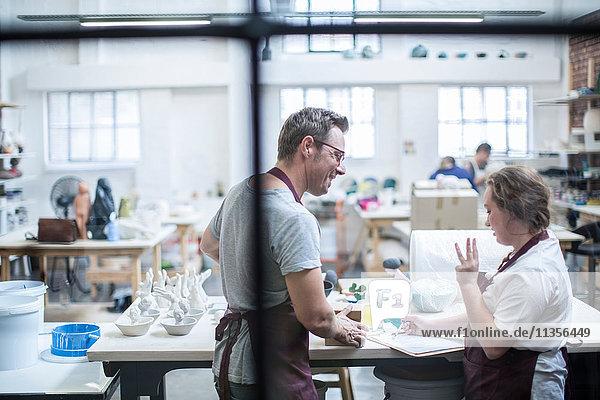 Fensteransicht einer Töpferlehrlingin  die in einem Workshop Ideen erklärt