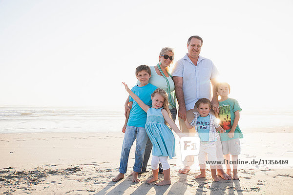 Family on beach looking at camera smiling