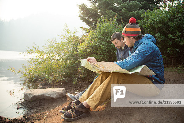 Two young male hikers reading map by lake  Mount Hood National Forest  Oregon  USA