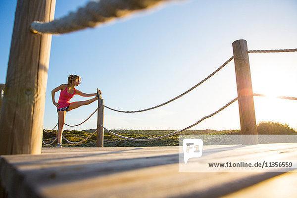 Junge Frau auf Holzbahn  Sport treiben  Bein strecken  niedriger Blickwinkel