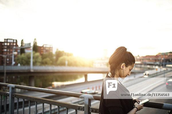 Seitenansicht der Frau mit dem Handy auf der Stehbrücke gegen den Himmel