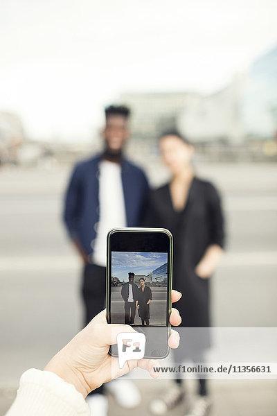 Abgeschnittenes Bild einer Frau  die Freunde in der Stadt fotografiert.