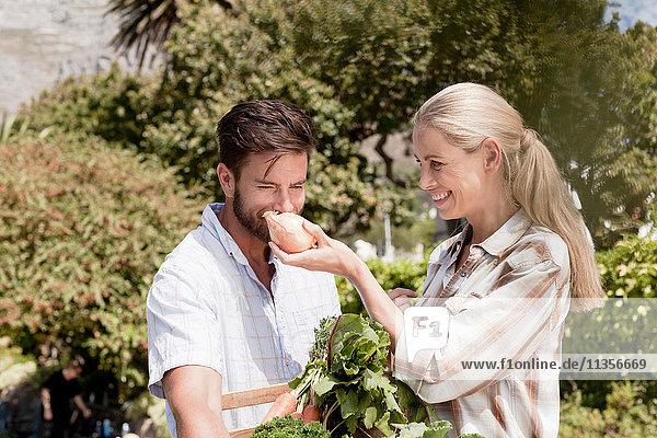 Reifes Paar im Garten  Frau hält frische Zwiebel für den Mann zum Riechen hoch