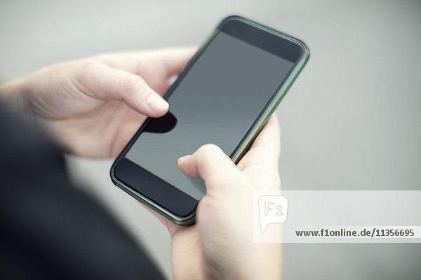 Abgeschnittenes Bild der Frau mit dem Smartphone