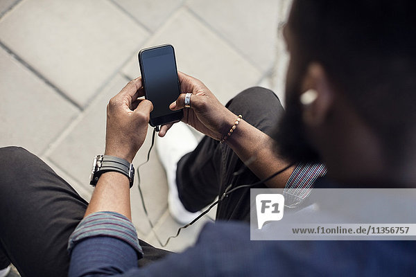 High angle view of man surfing the net on mobile phone