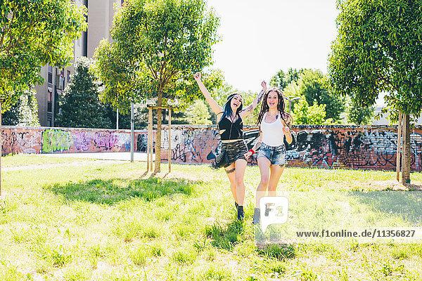 Zwei junge Frauen lachend und rennend im Stadtpark