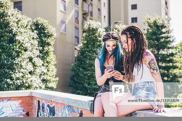 Zwei junge Frauen an der Wand beim Lesen von Smartphone-Texten in einer städtischen Wohnsiedlung