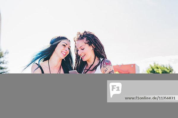 Zwei junge Frauen lachen über Smartphone-Texte in einer städtischen Wohnsiedlung