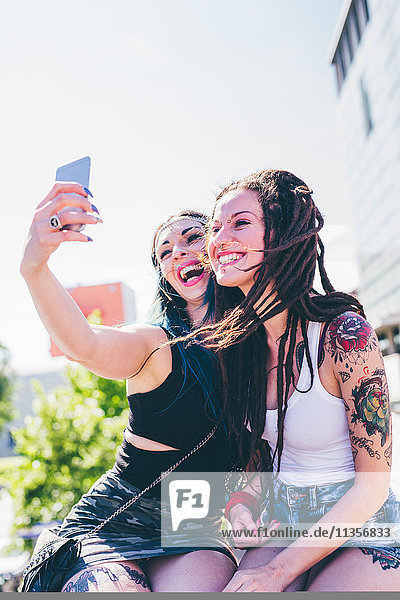 Zwei junge Frauen an der Wand nehmen Smartphone Selfie in städtischen Wohnsiedlung