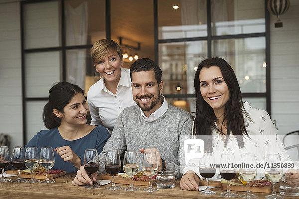 Portrait von lächelnden Geschäftsleuten bei der Weinprobe am Tisch