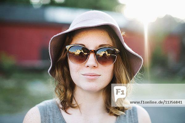Frau mit Sonnenbrille und Sonnenhut schaut in die Kamera