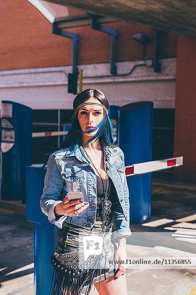Junge Frau mit tauchgefärbten blauen Haaren mit Smartphone in einer städtischen Wohnsiedlung