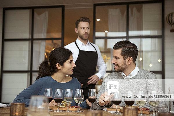 Geschäftsleute diskutieren bei einer Weinprobe gegen einen Mann  der eine Schürze trägt und wegschaut.