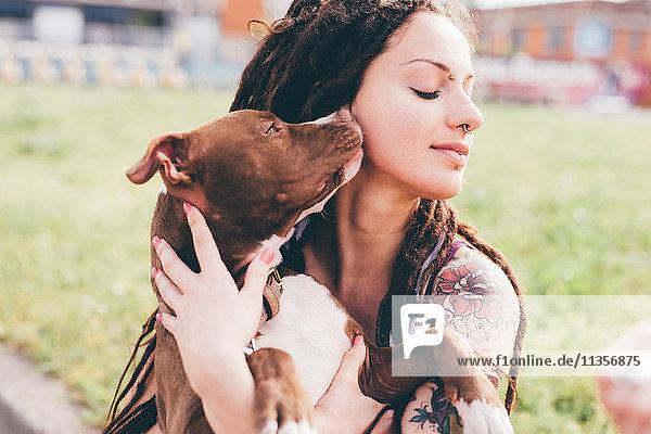 Pit Bull Terrier leckt tätowierte junge Frau im Stadtpark
