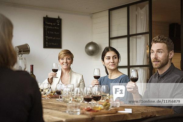 Lächelnde Geschäftsleute sitzen am Tisch und halten Weinglas.
