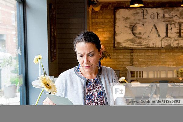 Reife Kundin liest Speisekarte im Cafe