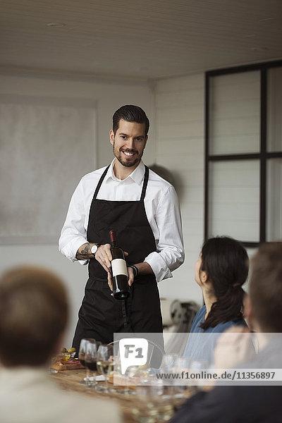 Glücklicher Mann  der Geschäftsleuten bei Tisch die Weinflasche zeigt.