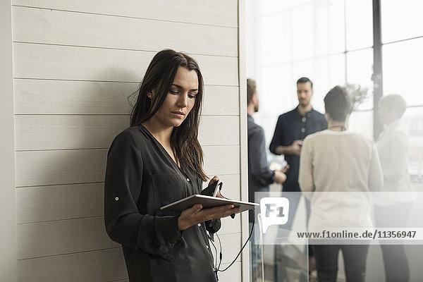 Frau hält digitales Tablett  während sie sich an die Wand lehnt  mit Menschen im Hintergrund